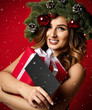 Leinwanddruck Bild - Beautiful woman with Christmas spruce fir wreath with cones and new year gift certificate present under snow flakes