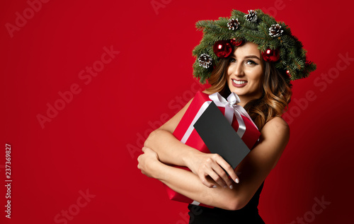 Leinwanddruck Bild Beautiful woman with Christmas spruce fir wreath with cones and new year gift certificate present happy smiling