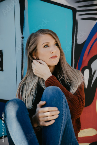 Portrait of Pretty Cute Young Blond Adult Woman Outside in Chilly Season Downtown Urban Street Art District Sitting in Front of Vibrant Colorful Graffiti Art Wall - 237376281