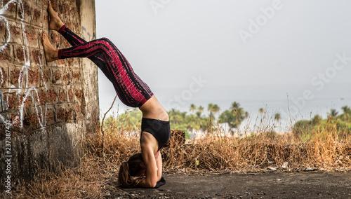 Fototapeta Yoga girl standing on her head in front of the ocean