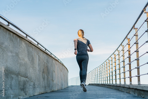 fitness, sport, people, exercising and lifestyle concept - woman running upstairs.
