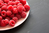 Fresh organic raspberry on a pink plate on black surface, low angle view. Close-up. Copy space.