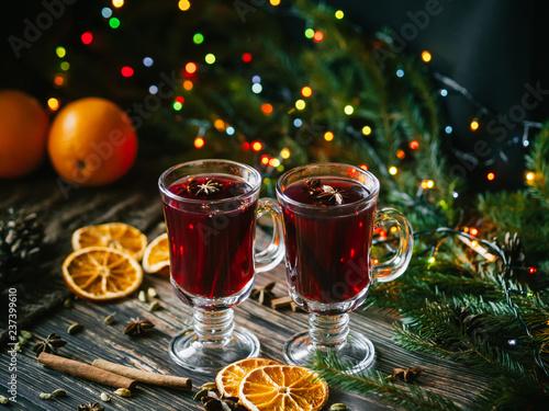 dwie szklanki ciepłego grzanego wina na drewnianym stole ozdobione Bożego Narodzenia. Plastry pomarańczy, cynamon, kardamon, goździki, anyż