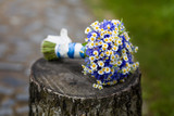 Wedding bouquet of cornflowers and daisies lies on the stump, wildflowers, blurred background.