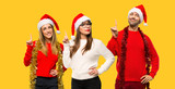 A group of people Blonde woman dressed up for christmas holidays showing and lifting a finger in sign of the best on yellow background - 237406041