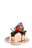 A biscuit cake is filled with chocolate with slices of chocolate tile, cherry and green leaf  isolated