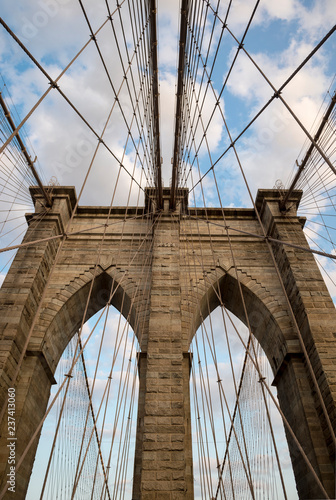 obraz PCV Scenic abstract view of the steel cables and textured bricks of the iconic stone arch tower of the Brooklyn Bridge under soft blue sky with sunset clouds