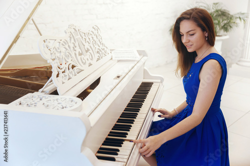 fototapeta na ścianę Closeup portrait of a girl in blue dress sitting at the piano and play the piano
