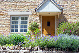 Light brown doors in a limestone golden colored English cottage with flowers and shrubs in a front garden, summer day . - 237441066