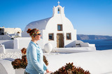A young woman stands against a white church on the famous romantic island of Santorini against the background of the Aegean Sea against a white background of a bright sunny day