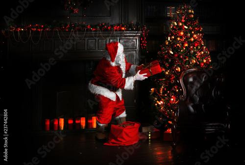 Foto Murales Christmas night, Santa Claus puts gifts under the tree