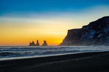 Iceland sunrise over black sand beach with cliffs