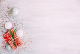 Christmas background with confetti, christmas balls, and red gift boxes on the white wooden board - 237451235