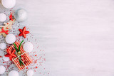 Christmas background with confetti, christmas balls, and red gift boxes on the white wooden board - 237451441