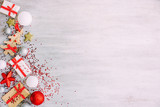 Christmas background with confetti, christmas balls, and red gift boxes on the white wooden board - 237451636