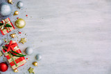 Christmas background with confetti, christmas balls, and red gift boxes on the white wooden board - 237457099