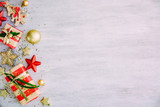 Christmas background with confetti, christmas balls, and red gift boxes on the white wooden board - 237457442