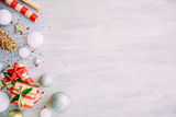Christmas background with confetti, christmas balls, and red gift boxes on the white wooden board - 237457831