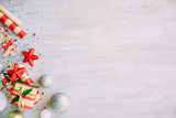 Christmas background with confetti, christmas balls, and red gift boxes on the white wooden board - 237457880