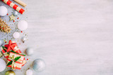Christmas background with confetti, christmas balls, and red gift boxes on the white wooden board - 237458031