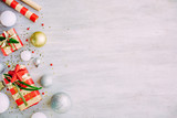 Christmas background with confetti, christmas balls, and red gift boxes on the white wooden board - 237458092