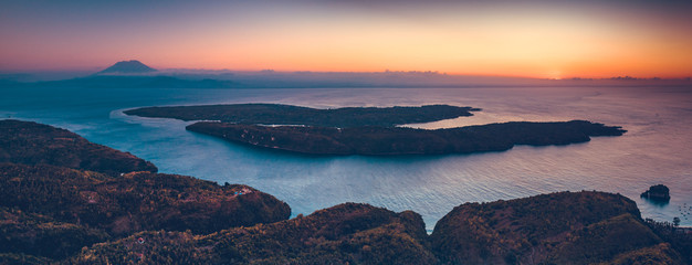 Sunset panorama rview of Indonesia shoreline and ocean. Aerial drone shot of Asian wild nature. Breathtaking landscape. Sunset over the Indonesian land and calm ocean. Bright colorful sky. © Goinyk