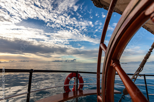 sailing cruise ship with steering wheel in front and indian ocean with cloudy sky