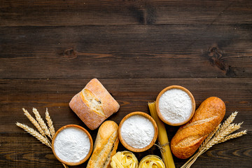 Bakery production, making bread and pasta. Fresh bread and raw pasta near flour in bowl and wheat ears on dark wooden background top view copy space