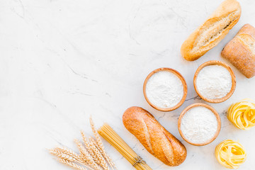 Bakery production, making bread and pasta. Fresh bread and raw pasta near flour in bowl and wheat ears on white stone background top view copy space