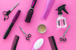 female hairdresser desk with accessories and combs on pink background top view