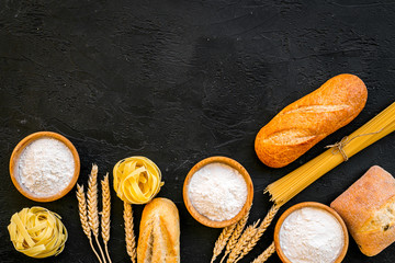 Farinaceous food. Fresh bread and raw pasta near flour in bowl and wheat ears on black background top view copy space