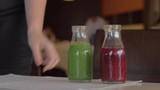 A closeup on healthy snacks being put on a table by a female hand. There are two small bottles of red and green smoothes, a cup of chia pudding and two halves of a kiwi - 237485840