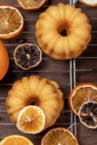 Small orange bundt cakes with fresh and dry oranges on cooling ruck, top view, flat lay, vertical composition