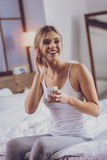 Beautiful young woman smiling widely while having coffee - 237493880