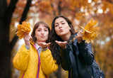 Pretty woman and teen girl are posing with bunch of maple's leaves in autumn park. They are training for kiss. Beautiful landscape at fall season. - 237502626