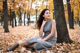 Pretty woman is sitting in autumn park near big tree. Beautiful landscape at fall season. - 237502897