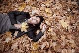Pretty woman is lying in autumn park on fallen leaves. Beautiful landscape at fall season. - 237503083