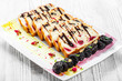 Pancakes with cream cheese, prunes, cherries decorated with chocolate and gold on plate on light wooden bacground. Traditional Russian cuisine at the Pancake week or Shrovetide. Flat lay. Top view