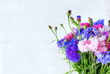 A beautiful bouquet of colorful cornflowers on a light background with copy space.