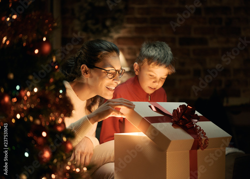 Leinwandbild Motiv Boy and his mother opening Christmas gifts