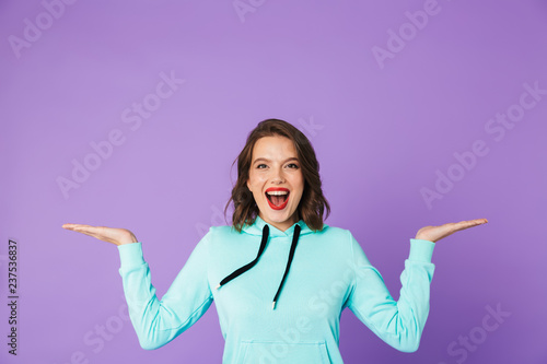 Leinwanddruck Bild Beautiful young woman posing isolated over purple background wall.
