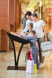 Familie am Touchscreen Informationskiosk