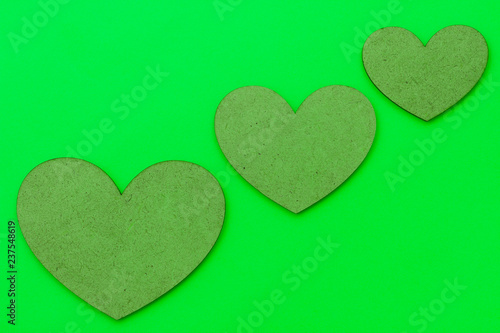 Three hearts of different sizes of brown color on a green background. Concept on the theme of love for Valentine's Day. - 237548619