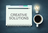 Word Creative Solutions on notepad. Business concept