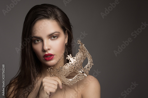 Fashion woman with long hair and red lipstick with golden mask. Dark background