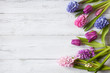 Flowers hyacinths and tulips on wooden white background