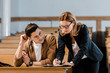 Leinwanddruck Bild - female teacher in glasses checking exam results of male student in classroom