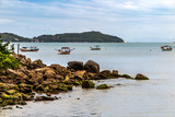 Morrinhos beach next to the rocks, with fishing boats and Macaco hill in the background, cloudy day, Bombinhas, Santa Catarina