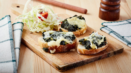 three cabbage and cheese bruschetta on wood board on table with salad