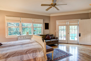 Tasteful bedroom interior with hard wood floors and french doors